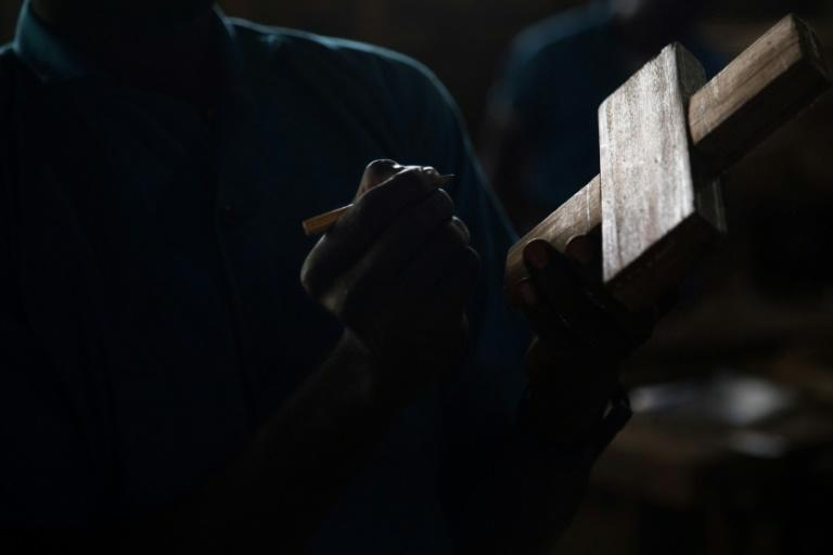 A former child soldier on a carpentry course draws a cutout on a piece of wood (AFP Photo/FLORENT VERGNES)