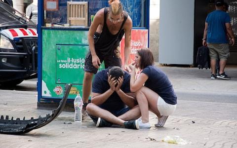 Injured people react after a van crashed into pedestrians in Las Ramblas, downtown Barcelona,