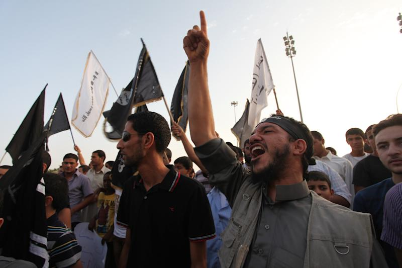 "Libyan followers of the Ansar al-Shariah Brigades chant anti-U.S. slogans during a protest in front of the Tibesti Hotel, in Benghazi, Libya, Friday, Sept. 14, 2012, as part of widespread anger across the Muslim world about a film ridiculing Islam's Prophet Muhammad. One of the leading suspects in an attack that killed the U.S. ambassador and three other Americans is the Libyan-based Islamic militant group Ansar al-Shariah, led by former Guantanamo detainee Sufyan bin Qumu. The group denied responsibility in a video Friday but did acknowledge its fighters were in the area during what it called a ""popular protest"" at the consulate, according to Ben Venzke of the IntelCenter, a private analysis firm that monitors Jihadist media for the U.S. intelligence community. (AP Photo/Mohammad Hannon)"