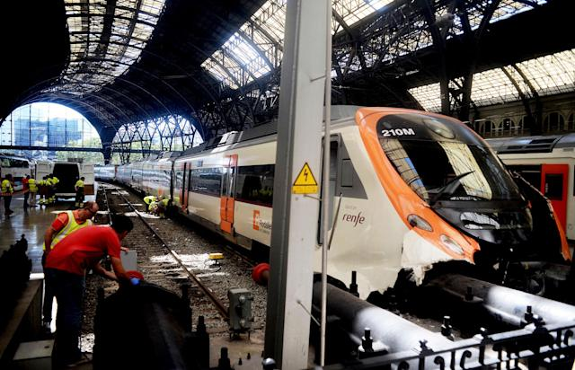 <p>Workers check a commuter train after it ran into the buffers on the platform of a train station in Barcelona, Spain, Friday July 28, 2017. (Photo: Adrian Quiroga/AP) </p>
