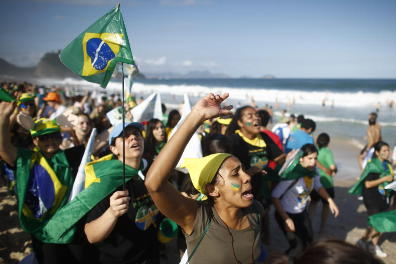 Pilgrims carrying a Brazilian flag sing on Copacabana beach in Rio de Janeiro, Brazil, Saturday, July 27, 2013. Pope Francis will preside over an evening vigil service on Copacabana beach that is expected to draw more than 1 million young people. (AP Photo/Victor R. Caivano)