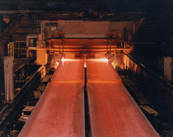 Sheet steel coming out hot from a furnace on a conveyor belt.