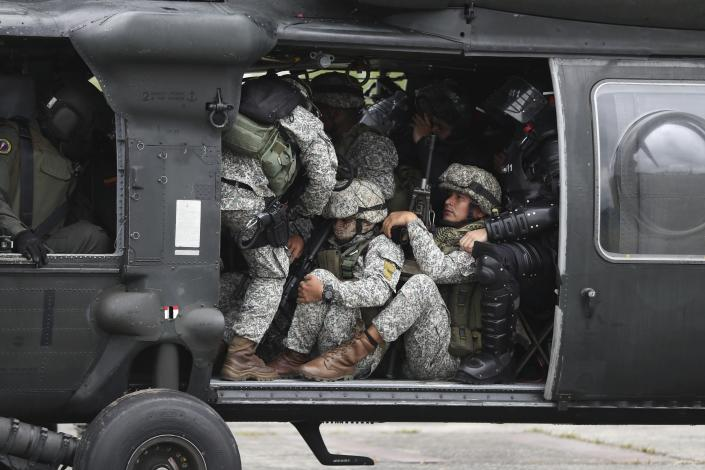 """Soldiers and National Police crowd into a helicopter as they prepare to lift off and travel to an illegal gold mining operation to destroy as part of the Armed Forces' """"Operation Guamuez III"""" in Magui Payan, Colombia, Tuesday, April 20, 2021. Illegal gold mining is common in Colombia, especially wildcat mines in poverty-stricken areas dominated by criminal gangs with little state presence. (AP Photo/Fernando Vergara)"""