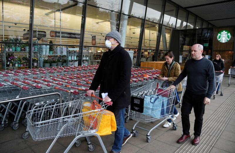 Shoppers queue to enter a Sainsbury's supermarket in West London