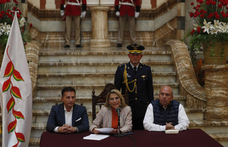 Bolivia's interim President Jeanine Anez, center, speaks during a press conference at the presidential palace, in La Paz, Bolivia, Thursday, Nov. 28, 2019. Accompanied by his Ministry of Defense Luis Fernando Lopez, left, and Government Minister Arturo Murillo, Anez reported today that she has determined to repeal Decree 4078, which authorized the military to participate in public restoration operations without having criminal responsibility for the use of force in situations of need and defense. (AP Photo/Juan Karita)
