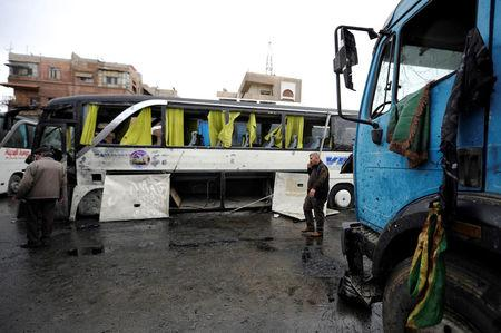 People inspect the damage at the site of an attack by two suicide bombers in Damascus