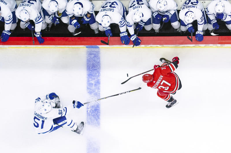 Nov 21, 2018; Raleigh, NC, USA; Carolina Hurricanes right wing Andrei Svechnikov (37) and Toronto Maple Leafs defenseman Jake Gardiner (51) chase after the puck at PNC Arena. The Carolina Hurricanes defeated the Toronto Maple Leafs 5-2. Mandatory Credit: James Guillory-USA TODAY Sports