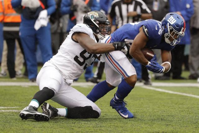 Jacksonville Jaguars defensive tackle Calais Campbell (93) tackles New York Giants' Saquon Barkley (26) during the first half of an NFL football game Sunday, Sept. 9, 2018, in East Rutherford, N.J. (AP Photo/Seth Wenig)