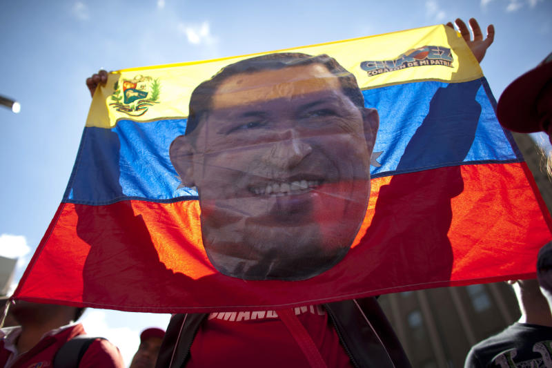 """A supporter of Venezuela's President Hugo Chavez holds up a banner bearing the image of the South American leader at a rally in Caracas, Venezuela, Thursday, Jan. 10, 2013. Hundreds of supporters gathered outside his presidential palace in an alternative inauguration, showing their support for the ailing leader and wearing T-shirts with the slogan """"I am Chavez."""" The government organized the rally for the cancer-stricken leader on the streets outside Miraflores Palace on what was supposed to be his inauguration day. A swearing-in ceremony has been indefinitely postponed, despite opposition complaints. (AP Photo/Ariana Cubillos)"""