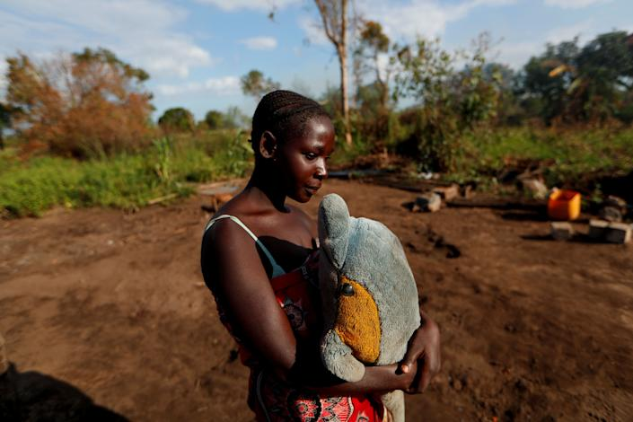 "Maria Jofresse, 25, holds a stuffed toy she received for her seventh birthday as she stands where her house stood, in the aftermath of Cyclone Idai, outside the village of Cheia, which means ""Flood"" in Portuguese, near Beira, Mozambique April 2, 2019. (Photo: Zohra Bensemra/Reuters)"