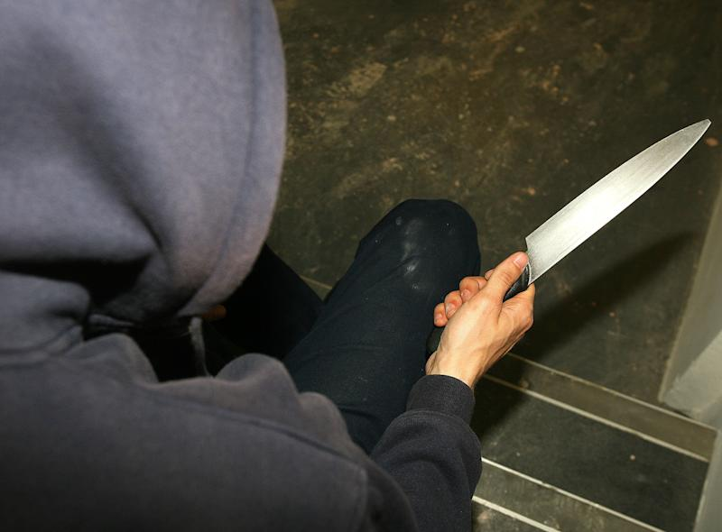 EMBARGOED TO 0001 SUNDAY AUGUST 18 PICTURE POSED BY MODEL File photo dated 25/04/09 of a man holding a knife, as courts will be given extra powers to tackle knife crime and serious violence, the Home Office has announced.