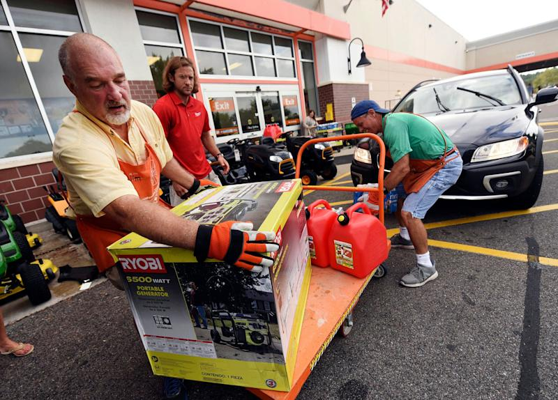 Jim Craig, David Burke and Chris Rayner load generators as people buy supplies at The Home Depot in Wilmington, North Carolina on Monday.