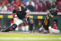 Pittsburgh Pirates' Hoy Park (68) scores a run ahead of the tag from Cincinnati Reds' catcher Tucker Barnhart (16) during the sixth inning of a baseball game in Cincinnati, Tuesday, Sept 21, 2021. (AP Photo/Bryan Woolston)