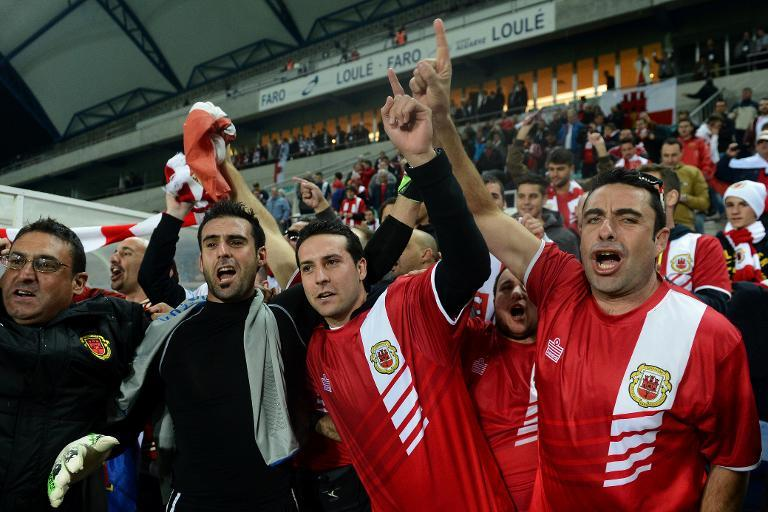 Gibraltar's goalkeeper Jordan Perez (2ndL) celebrates with supporters at the end of the World Cup 2014 friendly football match against Slovakia at Algarve stadium in Faro on November 19, 2013