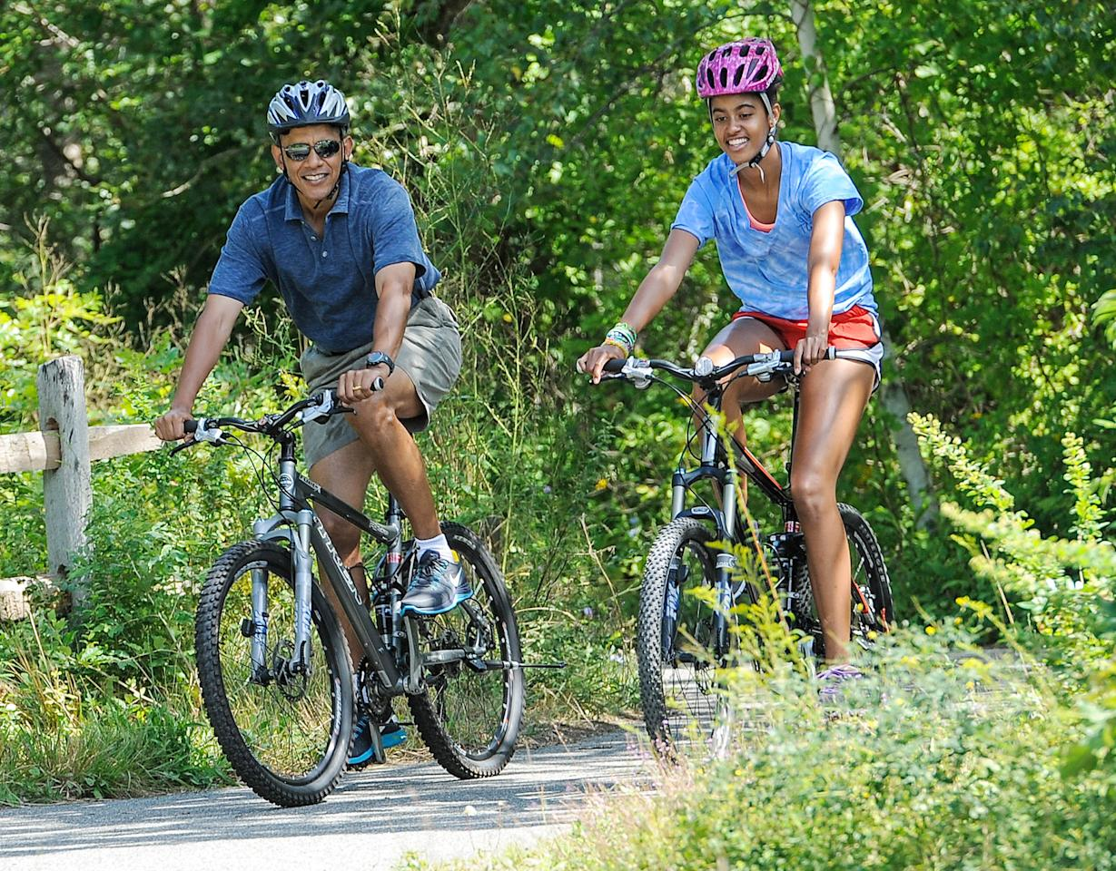 President Obama hit the bike trails with his older daughter, 15-year-old Malia, as the first family took their annual summer vacation to Martha's vineyard. (8/16/2013)