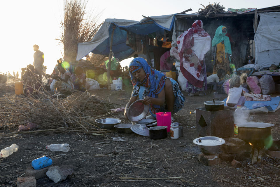 A Tigray refugee woman who fled the conflict in the Ethiopia's Tigray prepares breakfast for her family at Hamdeyat Transition Center near the Sudan-Ethiopia border, eastern Sudan, Thursday, Dec. 3, 2020. Ethiopian forces on Thursday blocked people from the country's embattled Tigray region from crossing into Sudan at the busiest crossing point for refugees, Sudanese forces said.(AP Photo/Nariman El-Mofty)