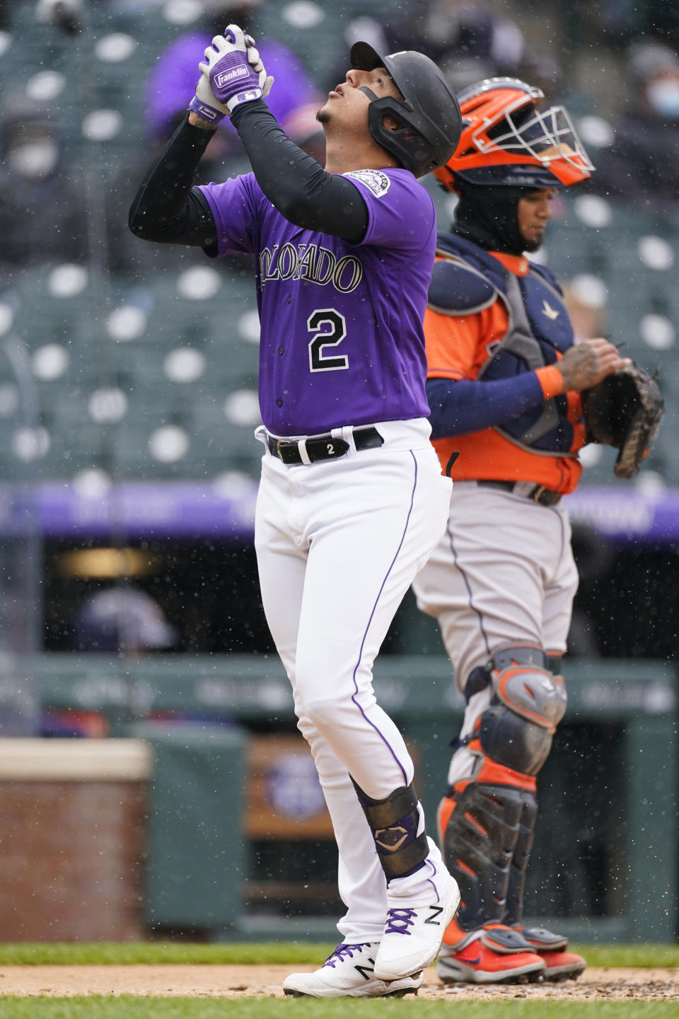 Colorado Rockies' Yonathan Daza, front, celebrates as he crosses home plate after hitting a solo home run as Houston Astros catcher Martin Maldonado looks on in the second inning of a baseball game Wednesday, April 21, 2021, in Denver. (AP Photo/David Zalubowski)