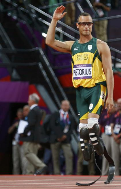 South Africa's Oscar Pistorius waves as he walks on to the track for the 400-meter semifinals. (Reuters)
