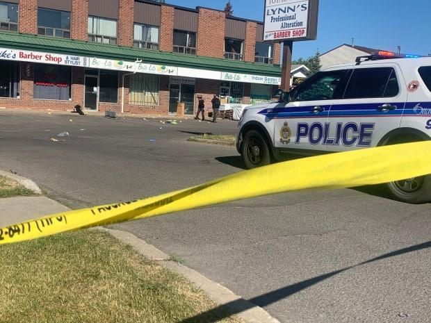 Ottawa police on scene at the corner of Meadowbrook and Cyrville roads, in the city's east end, early Sunday morning. The homicide unit is investigating after Warsama Youssouf, 27, was killed in the city's fourth shooting death in five days. (Natalia Goodwin/CBC - image credit)