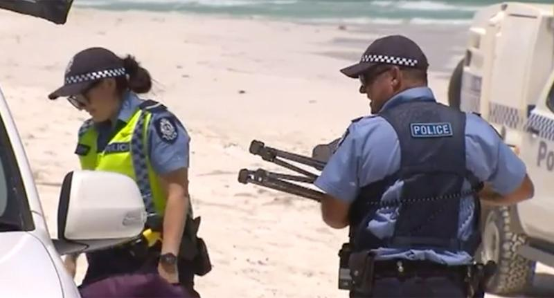 A police officer carries a tripod on White Island's beach.