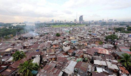 A sprawling shanty-town contrasts with high rise office buildings in Quezon city, suburban Manila