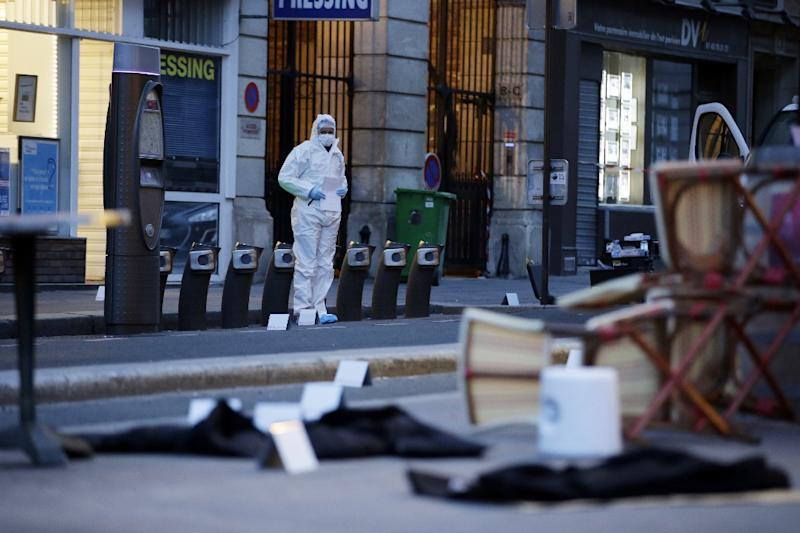 A forensic scientist at work outside the Cafe Bonne Biere on Rue du Faubourg du Temple on November 14, 2015, following a series of coordinated attacks in Paris late Friday (AFP Photo/Kenzo Tribouillard)