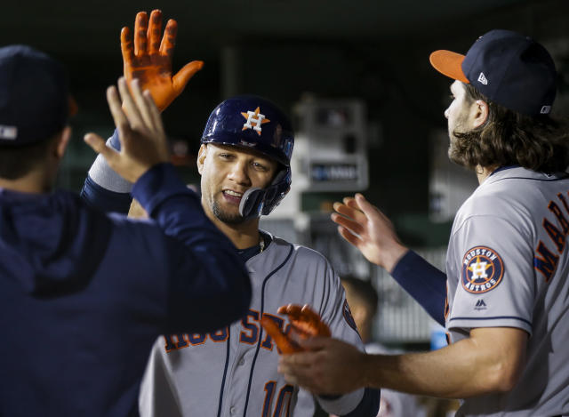 Houston Astros' Yuli Gurriel (10) is congratulated by teammates after scoring on a double by George Springer, not pictured, during the fifth inning of a baseball game against the Texas Rangers, Friday, April 19, 2019, in Arlington, Texas. (AP Photo/Brandon Wade)