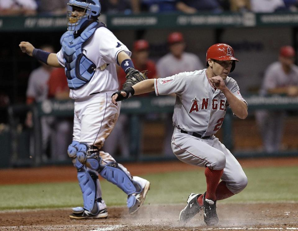 Los Angeles Angels' Peter Bourjos slides home in front of Tampa Bay Rays catcher Jose Molina on a seventh-inning, two-run single by teammate Erick Aybar off pitcher Jake McGee during a baseball game Tuesday, Aug. 27, 2013, in St. Petersburg, Fla. (AP Photo/Chris O'Meara)