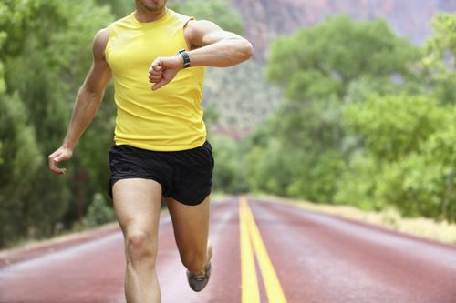 Man checking a fitness tracker on a run