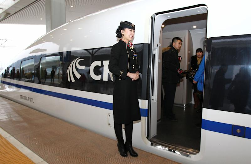 A file photo shows a conductor standing beside a new Chinese high speed train in Zhengzhou, Henan province, December 2012