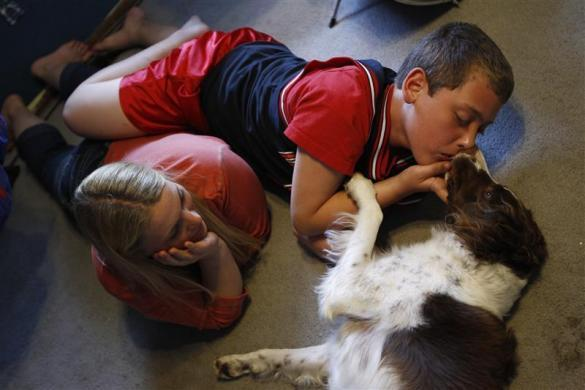 Parker Roos, who suffers from Fragile X, gets a kiss from his dog Daisy as his mother Holly looks on at their home in Canton, Illinois, April 4, 2012.