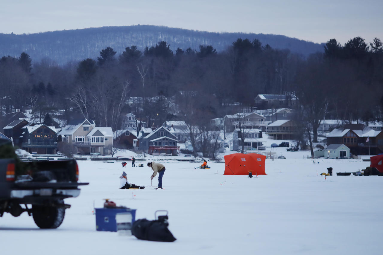 As dawn breaks over Pontoosuc Lake in Pittsfield, Mass., the ice fishing derby is well underway on Saturday, Jan. 19, 2019. A winter storm is inching its way toward New England after dumping snow and slowing travel for residents in the Midwest and Plains states. (Stephanie Zollshan/The Berkshire Eagle via AP)