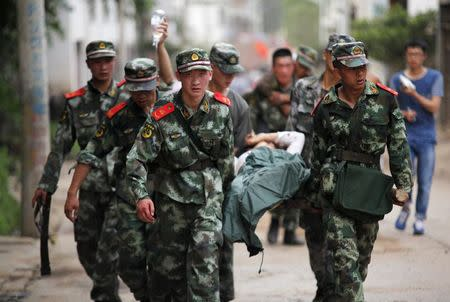 Paramilitary policemen carry an injured resident on a stretcher after an earthquake hit Ludian county of Zhaotong, Yunnan province August 3, 2014. REUTERS/China Daily