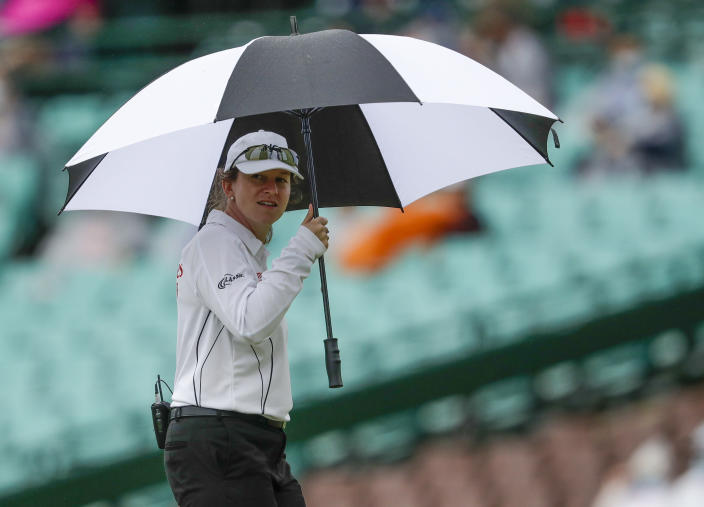 Claire Polosak inspects conditions as rain stops play during play on day one of the third cricket test between India and Australia at the Sydney Cricket Ground, Sydney, Australia, Thursday, Jan. 7, 2021. Polosak, became the first woman to officiate at a men's test on Thursday when she took up her role as fourth umpire for the match between Australia and India. (AP Photo/Rick Rycroft)