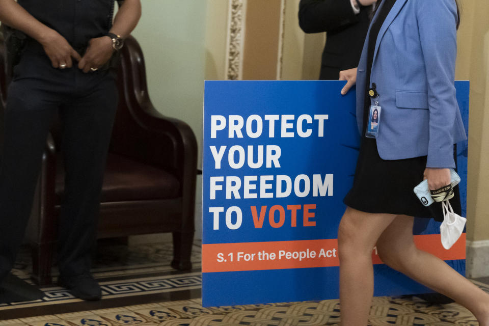 FILE - In this June 22, 2021, file photo, an aide carries a sign to the Senate floor before test vote on the For the People Act, a sweeping bill that would overhaul the election system and voting rights, at the Capitol in Washington. Both parties are bracing for a major legal fight over redistricting. Democrats need court wins more than Republicans because they control the redrawing of political maps in far fewer states than the GOP. (AP Photo/Alex Brandon, File)