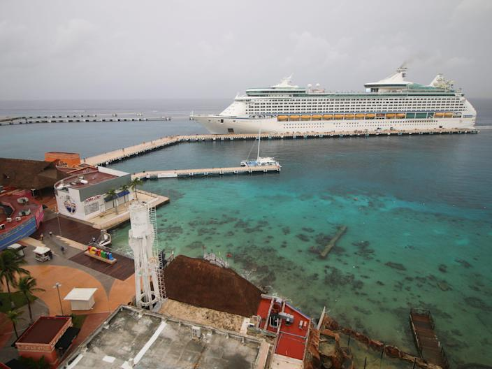 This image shows a cruise ship in the distance docked in Cozumel with buildings and palm trees and the beach in the foreground.