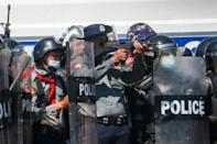 A police officer (C) aims a gun during clashes with protesters against the military coup in Naypyidaw on February 9, 2021