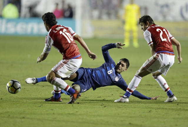 United States' Marky Delgado (8) slides while Paraguay's Cristian Riveros (16) and Oscar Romero (21) defend during the first half of an international friendly soccer match in Cary, N.C., Tuesday, March 27, 2018. (AP Photo/Gerry Broome)