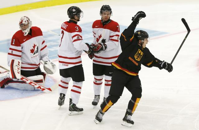 Germany's Sven Ziegler (R) celebrates his goal on Canada's goalie Jake Paterson (L) as Canada's Chris Bigras (3) and Josh Morrissey (7) react during the first period of their IIHF World Junior Championship ice hockey game in Malmo, Sweden, December 26, 2013. REUTERS/Alexander Demianchuk (SWEDEN - Tags: SPORT ICE HOCKEY)
