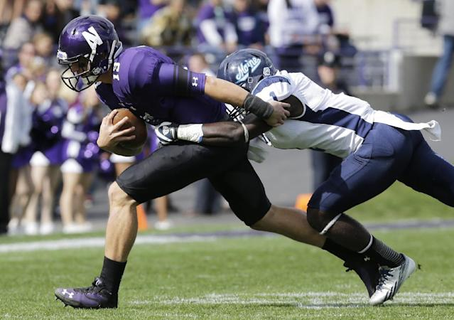Northwestern cornerback C.J. Bryant (13) is tackled by Maine defensive back Axel Ofori Jr (1)., during the first quarter of an NCAA college football game in Evanston, Ill., Saturday, Sept. 21, 2013. (AP Photo/Nam Y. Huh)