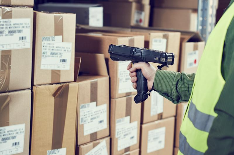 Warehouse worker scanning barcodes on one of many cardboard boxes.