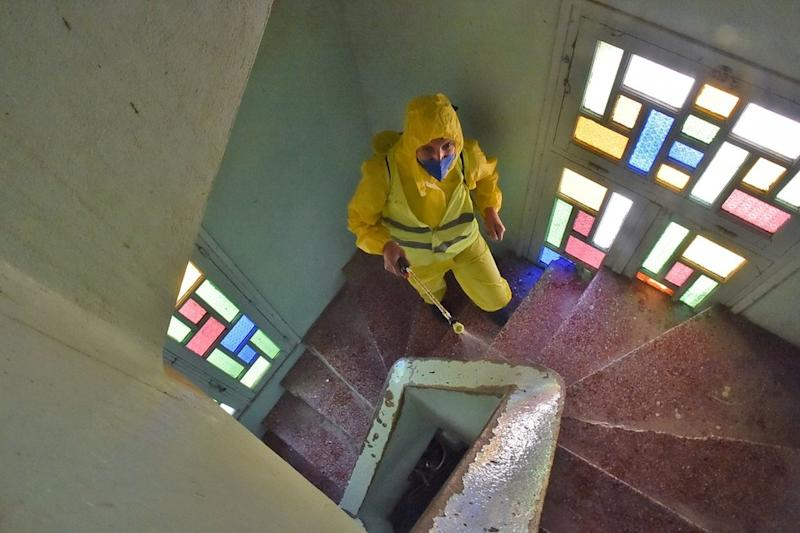 A man wearing a yellow PPE suit sprays mosque stairwell that is illuminated by coloured glass windows.