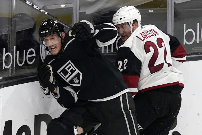Los Angeles Kings defenseman Austin Strand, left, collides with Arizona Coyotes left wing Johan Larsson during the second period of an NHL hockey game Wednesday, April 7, 2021, in Los Angeles. (AP Photo/Marcio Jose Sanchez)