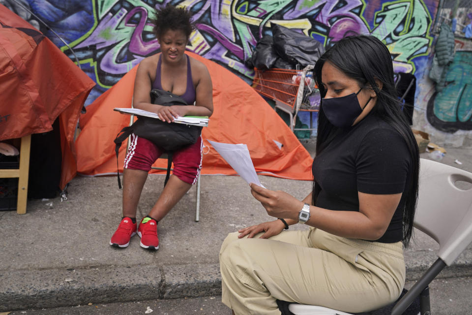 """Yessenia Benitez, a 30-year-old licensed clinical social worker, tries to help a homeless woman sort through some documents near a homeless encampment in the Queens borough of New York, Wednesday, April 14, 2021. """"Right now, they are adapting by collecting bottles but they are working folks. They want to contribute to society. And before the pandemic, they were contributing to society, some of them were paying taxes,"""" said Benitez. (AP Photo/Seth Wenig)"""