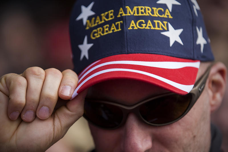 A Trump supporter dons a hat at an Ohio campaign rally. Photo from Getty Images