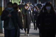 Commuters wearing face masks to protect against the coronavirus walk along a street in Beijing, Thursday, Oct. 22, 2020. The number of confirmed COVID-19 cases across the planet has surpassed 40 million, but experts say that is only the tip of the iceberg when it comes to the true impact of the pandemic that has upended life and work around the world. (AP Photo/Mark Schiefelbein)