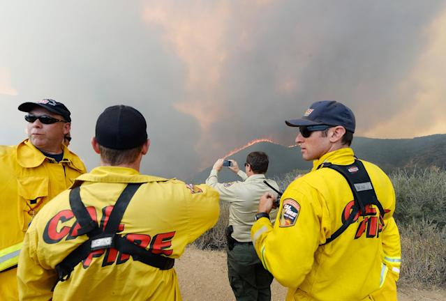NEWBURY PARK, CA - MAY 03: Firefighters look on as wildfire charges back up from Sycamore Canyon inside Pt. Mugu State Park due to changing winds on May 3, 2013 in Newbury Park, California. Hundreds of firefighters are battling wind and dry conditions with over 10,000 acres already burned. (Photo by Kevork Djansezian/Getty Images)