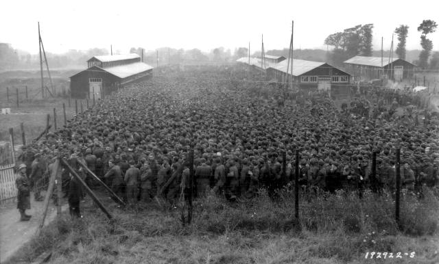 <p>German prisoners of war captured after the D-Day landings in Normandy are guarded by U.S. troops at a camp in Nonant-le-Pin, France, on Aug. 21, 1944. (Photo: U.S. National Archives/handout via Reuters) </p>