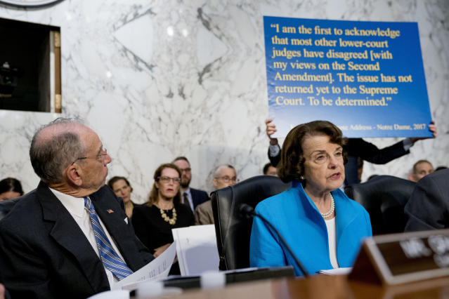 A poster depicting a 2017 quote on the Second Amendment by President Trump's Supreme Court nominee, Brett Kavanaugh, is held up behind Sen. Dianne Feinstein, D-Calif., as she questions Kavanaugh on Capitol Hill in Washington on Thursday, the second day of his confirmation hearings. Senate Judiciary Committee Chairman Chuck Grassley, R-Iowa, looks on. (Photo: Andrew Harnik/AP)