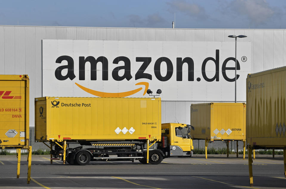 FILE - In this file photo dated Wednesday, Nov. 14, 2018, post trucks leaves the Amazon Logistic Center in Rheinberg, Germany. Germany's antitrust agency said Thursday Nov. 29, 2018, it has begun an investigation into online retailer Amazon over complaints that it's abusing its dominant position to the detriment of other sellers using its platform. (AP Photo/Martin Meissner, FILE)